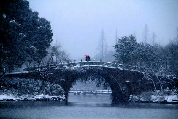 A couple with pink umbrella on a snowy bridge at West Lake